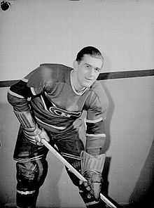 Maurice Richard poses for a photographer while wearing his full Canadiens uniform.
