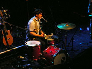 Mumford & Sons - The band members play multiple instruments in live performances. Here Marcus Mumford sits at a drum kit.