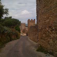 Walls and towers along a narrow, curved street