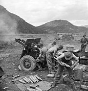 Soldiers firing a howitzer against a mountainous backdrop.