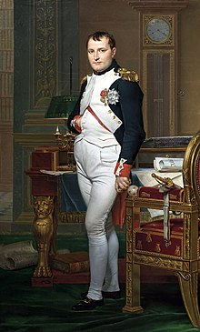 Full length portrait of Napoleon in his forties, in high-ranking white and dark blue military dress uniform. He stands amid rich 18th-century furniture laden with papers, and gazes at the viewer. His hair is Brutus style, cropped close but with a short fringe in front, and his right hand is tucked in his waistcoat.