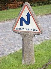 Cartello concreto che indica una successione di curve oltre 400 metri