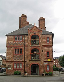 The end of a block of three-storey flats with an arched area on each floor, terracotta dressings and brick diapering.