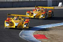 Two bright yellow racing sports cars on a race track taking a left hand corner