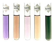Five liuids in glass bottles: violet, label Pu(III); dark brown, label Pu(IV)HClO4; light purple, label Pu(V); light brown, label Pu(VI); dark green, label Pu(VII).
