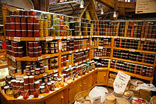In the lower portion of the photograph is a light-coloured wooden cabinet with closed doors, above which are three levels of shelving fully stacked with glass jars containing preserves, jams, and pickled foods. Labels are affixed to the front of each wooden shelf below the stacked jars. At the top of the photograph are some of the timber support beams of the structure.