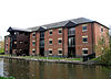 A brick building by the canal with three storeys and a loading bay on the left protruding towards the canal.