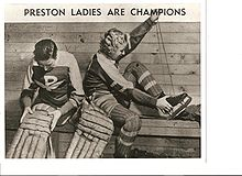 two women putting on hockey equipment