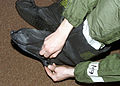 Putting on his cover boots, Airman (AMN) Kevin Camara, USAF, 2nd Communications Squadron (CS), prepares for Chemical Warfare Training, at Barksdale AFB, Louisiana 020301-F-JG870-002.jpg
