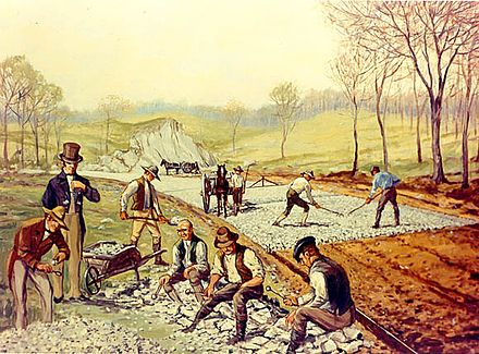 "Construction of the first macadam road in the United States (1823). In the foreground, workers are breaking stones ""so as not to exceed 6 ounces in weight or to pass a two-inch ring"". Rakeman - First American Macadam Road.jpg"