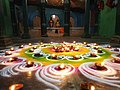 Rangoli with small lamps in a puja at a temple.jpg