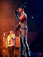 A young woman with black short hair is singing into a microphone on a stand while wearing a leather outfit