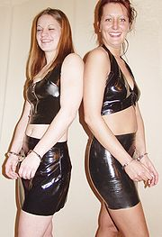 Two women in handcuffs and latex miniskirts and tops