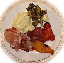 Un secondo piatto con speck, prosciutto crudo, purea di patate e verdure alla griglia.