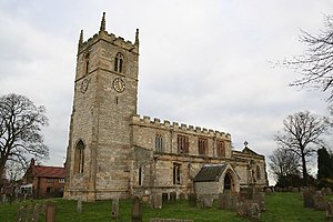 A stone church seen from the southwest.  On the left is the tower with a battlemented parapet and pinnacles, in the centre is the nave, also battlemented, and to the right  at a lower level is the chancel