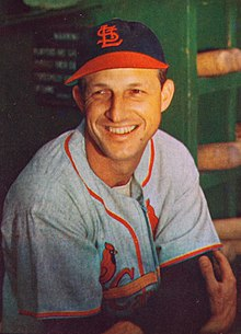 A playing-age Stan Musial in his baseball uniform, looking to the left and smiling