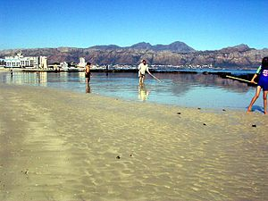 Strand, Western Cape - Sandy beach with tidal pool along the Beach Road in Strand with Gordon's Bay and the Hottentots Holland Mountains in the background