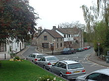 Street scene showing grass area to the left of road junction. Ahead are buildings.