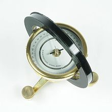 Photograph. The most prominent feature is a horizontal circular compass case that is seen from above. The compass is centered inside of a black ring with a square cross-section. The compass and ring are supported on a brass tripod that has leveling screws as its feet.