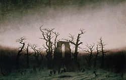 A painting in a yellow and brown palette of a ring of bare tree trunks surrounding a ruined abbey with gravestones on the ground.