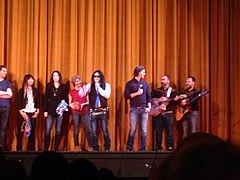 Wiseau and Sestero with microphones on the theatre stage with multiple musicians behind them.