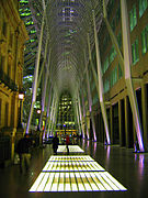 A towering metal gridwork catenary arch forms a gallery over a shiny concrete concourse inset with glowing grids of glass. Beyond the arch, city lights of tall buildings are visible. A four-story historic stone buildign stands to the left; a plain modern building rises out of sight to the right.