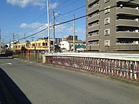 Train of Nishitetsu-Kaizuka Line near Tonoharu Station from Hamadabashi Bridge.JPG