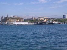 Two ships in Kadıköy and the Haydarpaşa Train Station behind.jpg