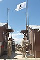 U.S. Army Spc. Nick Tangey, right, an information technology specialist with the 703rd Brigade Support Battalion, 4th Infantry Brigade Combat Team, 3rd Infantry Division, raises the Wounded Warrior flag over 130504-A-FN421-004.jpg
