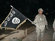U.S. Army soldier with captured ISIS flag in Iraq, December 2010