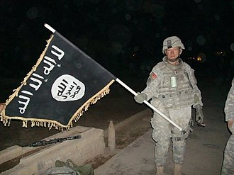 Islamic State of Iraq and the Levant - U.S. Army soldier with captured ISI flag in Iraq, December 2010