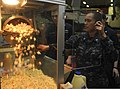 U.S. Navy Personnel Specialist 3rd Class Julia Barrios, right, and Hull Maintenance Technician 2nd Class Mitchell Gunderson make popcorn for movie night in the hangar bay of the aircraft carrier USS Nimitz (CVN 130825-N-AZ866-096.jpg