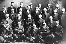 A large group of white men in suits posing for a picture