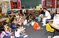 US Navy 030512-N-7217H-001 Mess Management Specialist Gui Gagui, Armed Forces Committee Chairperson, reads a book to a group of 1st grade students at E.J. King Elementary School.jpg