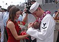 US Navy 031102-N-1618Z-103 Greeted by his wife and daughter, Operation's Specialist 3rd Class Jeromy Turner holds his ten-day-old daughter for the first time upon his arrival home from deployment aboard the USS Chosin (CG 65).jpg