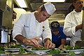 US Navy 040428-N-5579M-004 Executive Chef James Reaux puts the final touch on a Crisp Hydro-Arugula salad.jpg