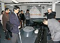 US Navy 060201-N-9860Y-129 Boatswain's Mate 1st Class David A. Slodysko describes the anchor chain of the 7th Fleet Command and Control ship, USS Blue Ridge (LCC 19) to a group of Japanese students and professors from several N.jpg