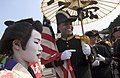 US Navy 061103-N-9851B-003 Master-at-Arms 1st Class Marcus Watkins, dressed as a member of Commodore Matthew C. Perry's crew, holds a Japanese kasa as he talks with Japanese participants of the Tokyo.jpg