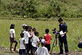 US Navy 070626-N-6410J-066 Children flock to Mass Communication Specialist 3rd Class Leonard Mandap as he begins to videotape the progress made at the Honest Anislag Duraga Transition Center in support of Pacific Partnership 20.jpg