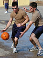 US Navy 080112-N-7367K-010 Builder 3rd Class Ryan Richards, assigned to Naval Mobile Construction Battalion (NMCB) 1, tries to dribble past Construction Mechanic 3rd Class Jacob Bockhorn in a basketball game during the detachme.jpg