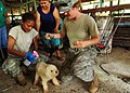US Navy 100822-N-1531D-190 Army Maj. Heather Shuey-Burton, right, from Lenexa, Kan., and Pfc. Angela McCormick, from Sacramento, Calif., spray flea-removal on a dog during a veterinary visit to a local farm in Costa Rica.jpg