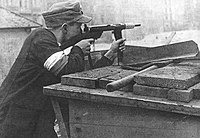 Polish insurgent, wearing armband in the national colours, at a Warsaw Uprising barricade. He is using the Polish submachine gun Błyskawica.