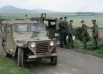 Group of three United States soldiers, one armed with a rifle, and two West German Bundesgrenzschutz officers standing by two vehicles parked on a narrow asphalted road in a rolling landscape with fields and hills visible behind them.
