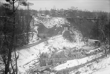 Construction across a bare valley; a bridge being built. The ground is covered in snow. In the background, an iron tressel carries cars over the valley.
