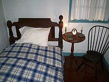 Photo en couleur d'une chambre avec un lit, une table et une chaise