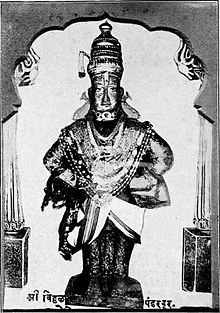 A black and white photograph of a stone icon of an arms-akimbo man standing on a brick and wearing a dhoti, angarkha (shirt), uparna (cloth that flows over both his hands), a crown, fish-shaped earrings and long necklaces till his waist.