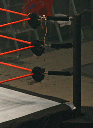 Wrestling ring - The corner structure of a WWE ring, showing the attachment of the ring ropes to the ring post via the padded turnbuckles