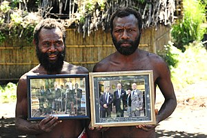 Prince Philip Movement - Yaohnanen tribesmen show pictures of 2007 visit with Prince Philip