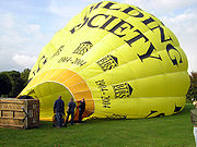 A hot air balloon is partially inflated with cold air from a gas-powered fan, before the propane burners are used for final inflation.