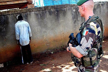A Foreign Legion soldier with a captured rebel, Ivory Coast, 10 August 2004. - French Foreign Legion